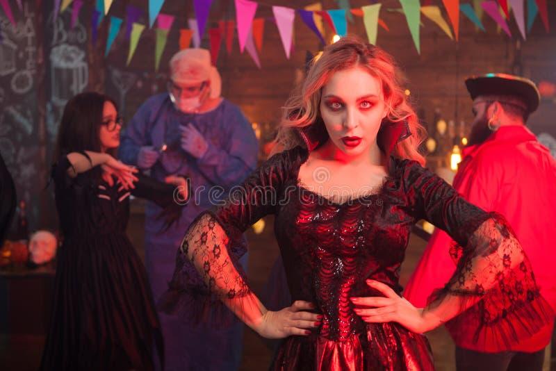 Mujer joven atractiva que presenta a la cámara en traje de la bruja en la celebración de Halloween fotografía de archivo