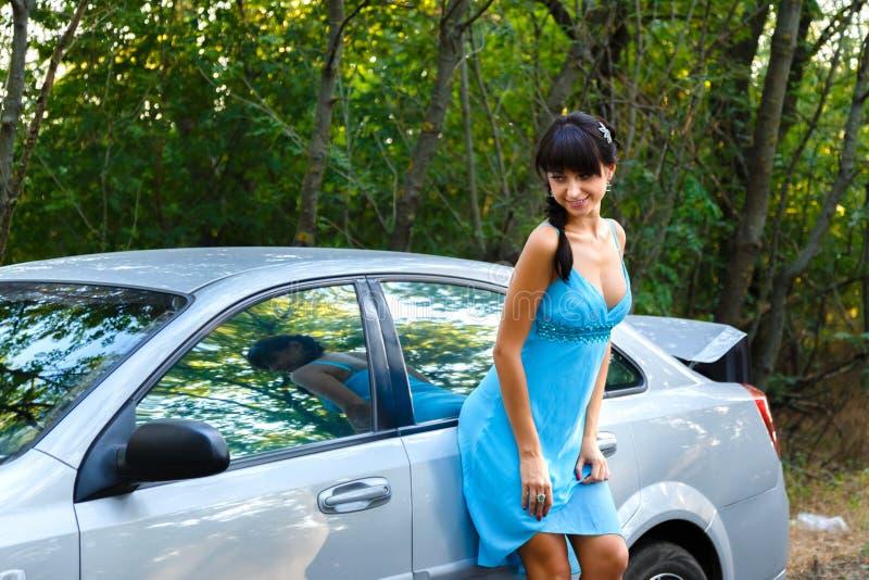 Mujer joven atractiva que se coloca en el camino cerca del coche blanco fotos de archivo