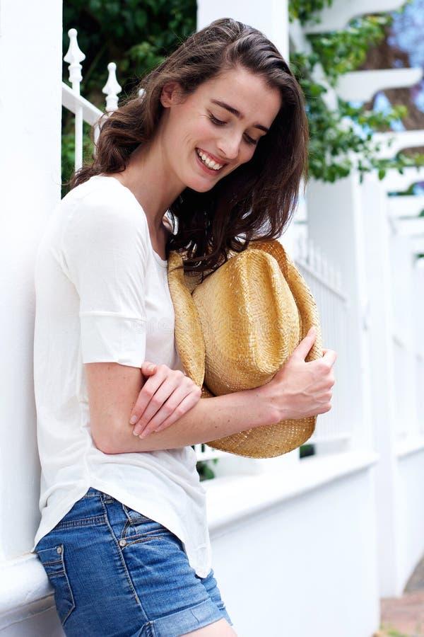 Mujer joven atractiva que se inclina contra la cerca que sostiene el sombrero de vaquero fotografía de archivo