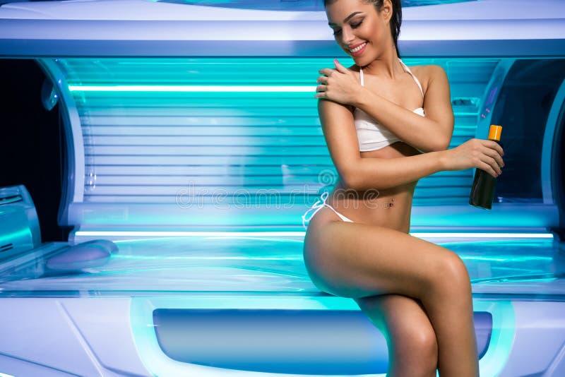 Mujer joven atractiva que se prepara para broncear en solarium fotos de archivo
