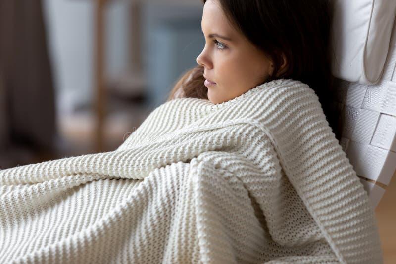Mujer joven atractiva que se relaja debajo de la manta suave en silla cómoda imagenes de archivo