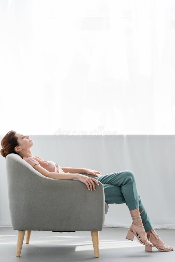 mujer joven atractiva que se relaja en la butaca cómoda foto de archivo