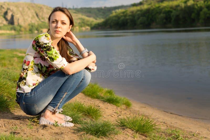 Mujer joven atractiva que se sienta al lado de un lago imágenes de archivo libres de regalías