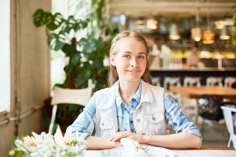 Mujer joven atractiva que se sienta en café y la sonrisa foto de archivo