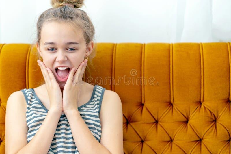 Mujer joven atractiva que se sienta en el sofá en casa con la expresión de la sorpresa en la cara imagen de archivo