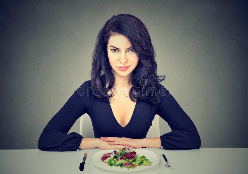 Mujer joven atractiva que se sienta en la ensalada verde preparada de la tabla fotografía de archivo libre de regalías
