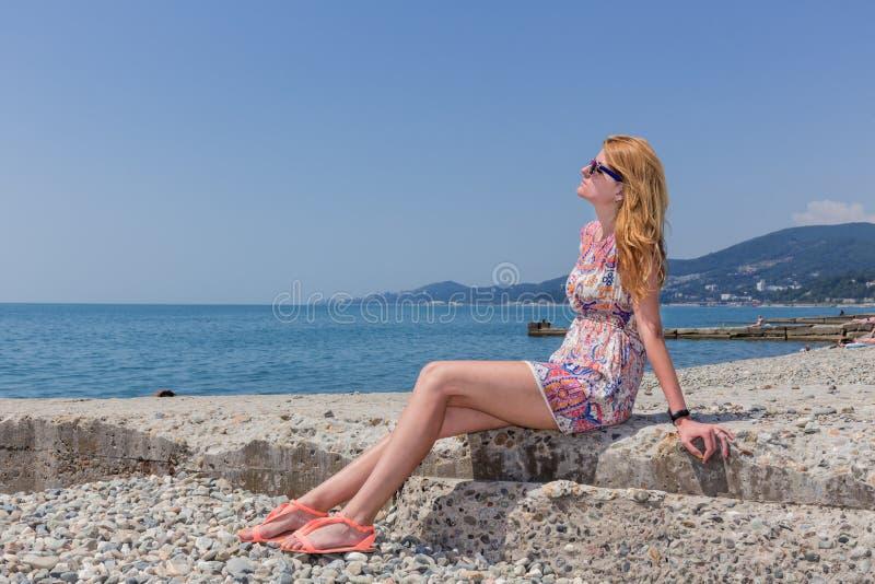 Mujer joven atractiva que se sienta en la playa imágenes de archivo libres de regalías