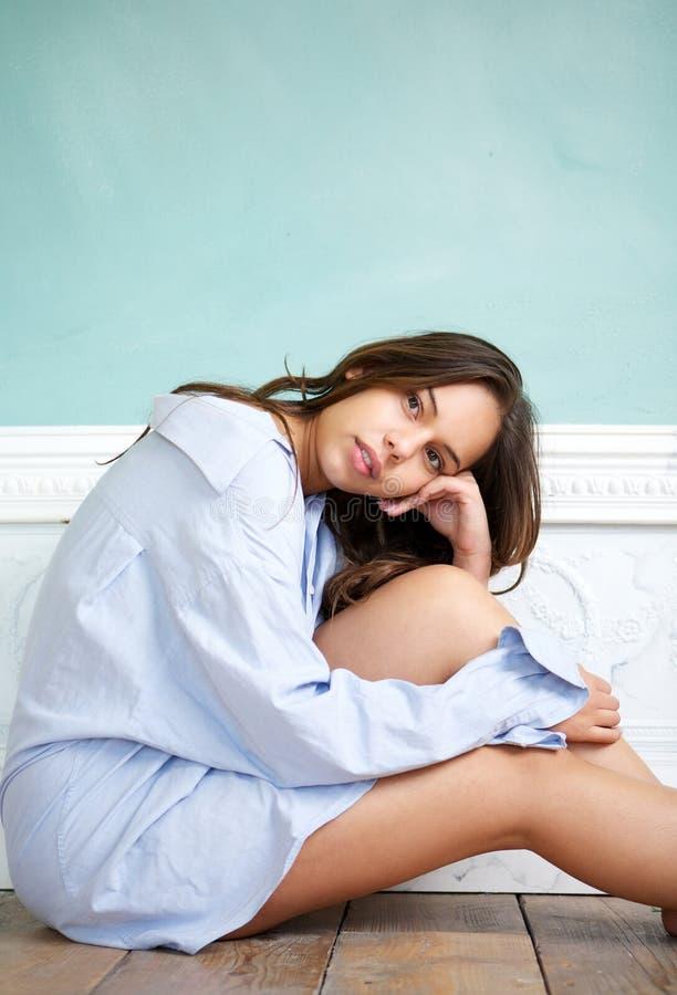 Mujer joven atractiva que se sienta en piso de madera y que se relaja en casa imagen de archivo