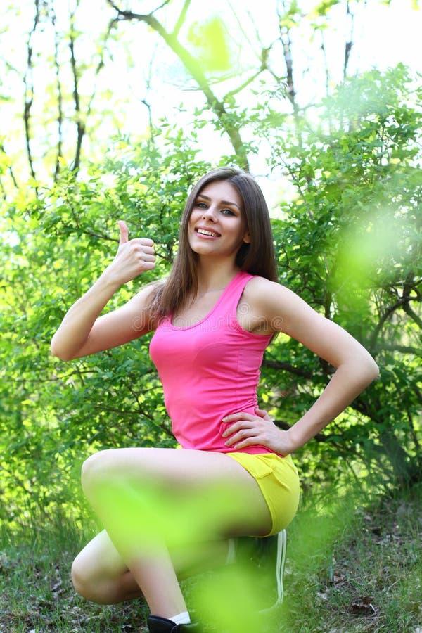 Mujer joven atractiva que se sienta en un parque del verano y que hace el s foto de archivo libre de regalías