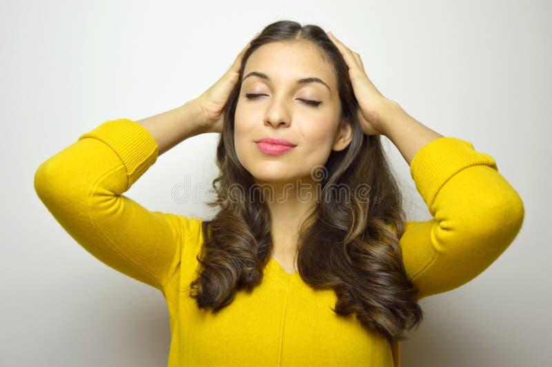 Mujer joven atractiva que sonríe con los ojos y las manos del cierre entre el pelo suave en fondo gris imagenes de archivo