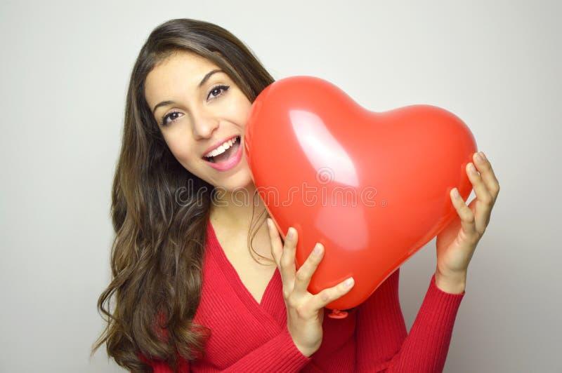 Mujer joven atractiva que sostiene el balón de aire rojo del corazón en fondo gris Concepto del día del ` s de la tarjeta del día imágenes de archivo libres de regalías