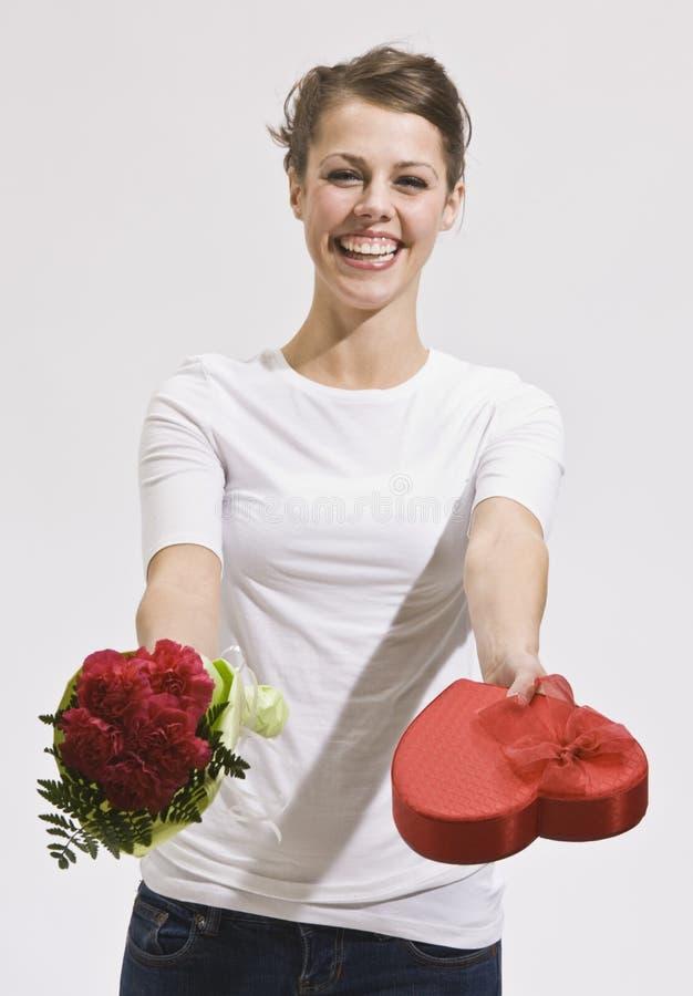 Mujer joven atractiva que sostiene hacia fuera rosas y el caramelo imagen de archivo libre de regalías