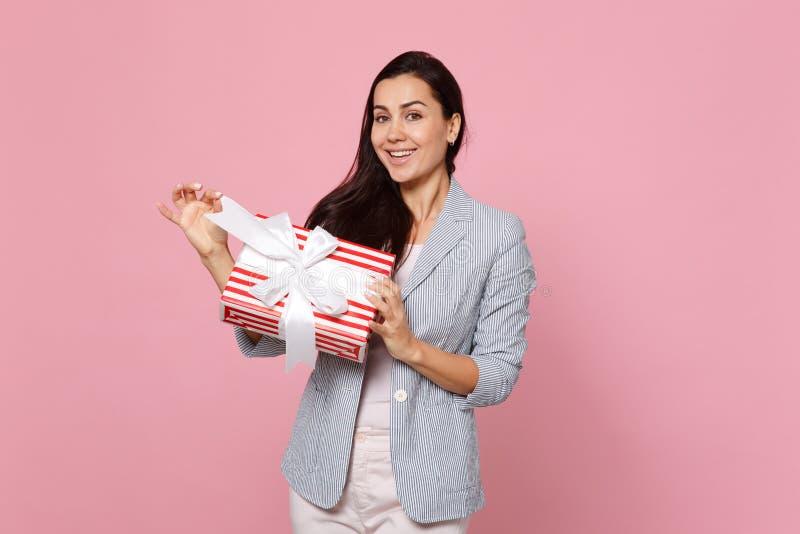 Mujer joven atractiva que sostiene la actual caja rayada roja con la cinta del regalo aislada en fondo en colores pastel rosado S fotografía de archivo