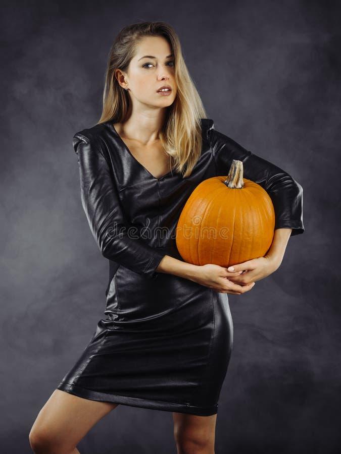 Mujer joven atractiva que sostiene la calabaza para Halloween imagenes de archivo