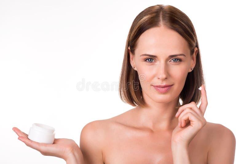 Mujer joven atractiva que sostiene la crema imágenes de archivo libres de regalías
