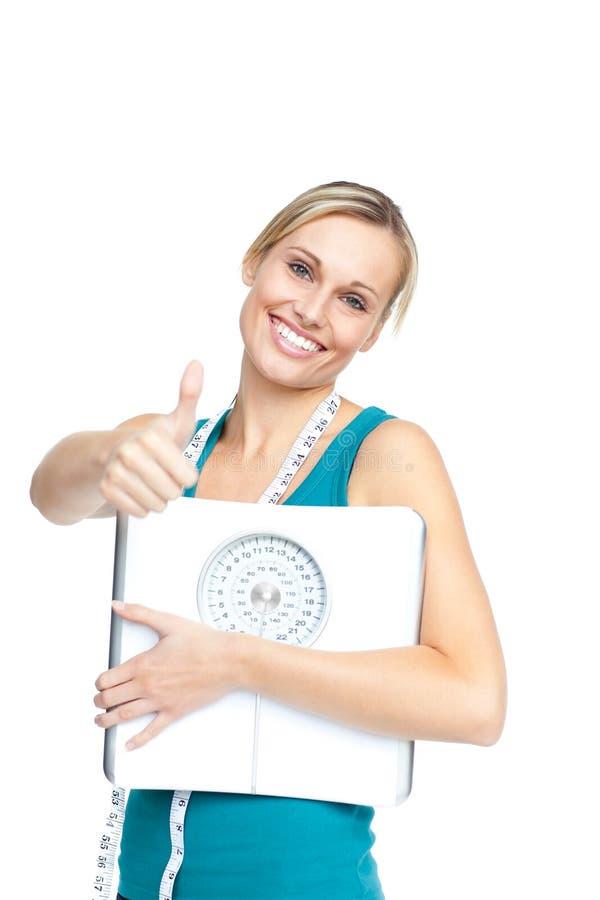 Mujer joven atractiva que sostiene una escala del peso imagenes de archivo