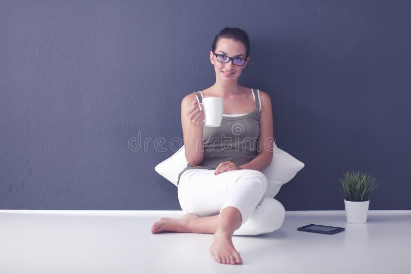 Mujer joven atractiva que sostiene una taza de café y que sonríe mientras que se sienta en el piso imagenes de archivo