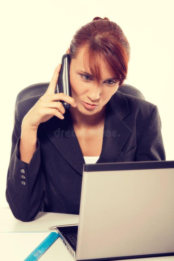 Mujer joven atractiva que tiene negociaciones por el teléfono en oficina imagenes de archivo