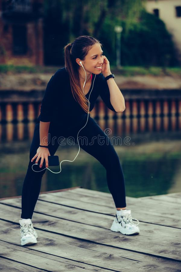 Mujer joven atractiva que toma la rotura después de activar mientras que escucha la música en su teléfono elegante fotografía de archivo
