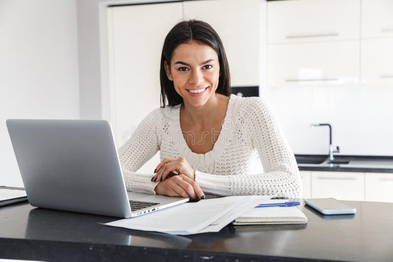 Mujer joven atractiva que trabaja con el ordenador portátil fotografía de archivo