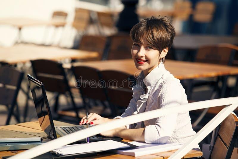 Mujer joven atractiva que usa la computadora portátil foto de archivo