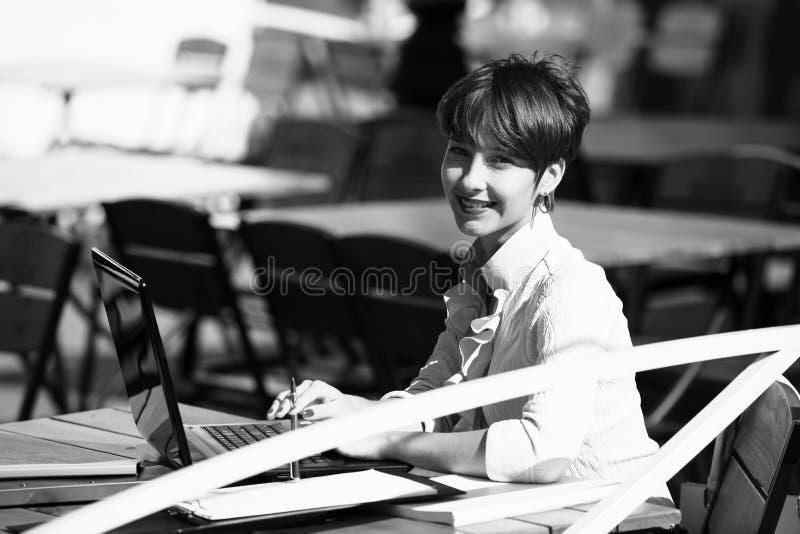 Mujer joven atractiva que usa la computadora portátil fotografía de archivo