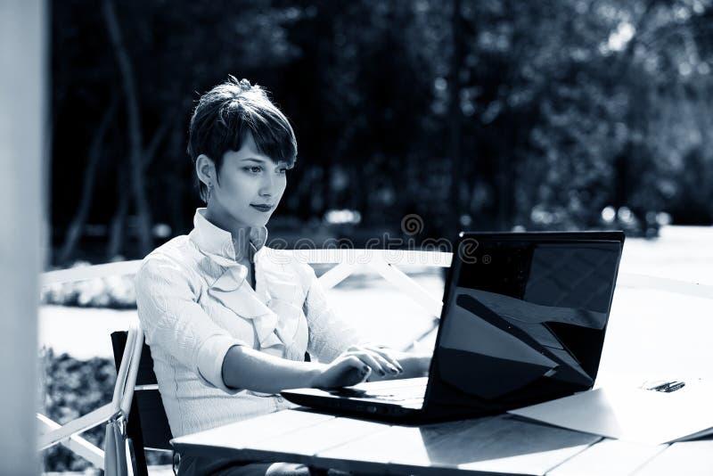 Mujer joven atractiva que usa la computadora portátil imagen de archivo
