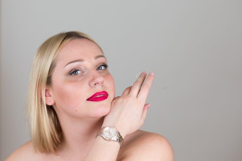 Mujer joven atractiva rubia en backgounds grises del estudio foto de archivo
