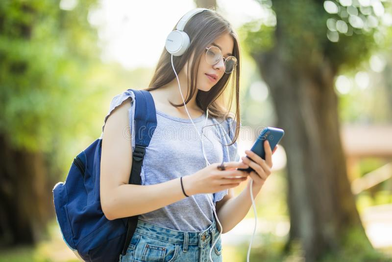 Mujer joven atractiva sonriente con la mochila que escucha la música del teléfono en parque foto de archivo libre de regalías