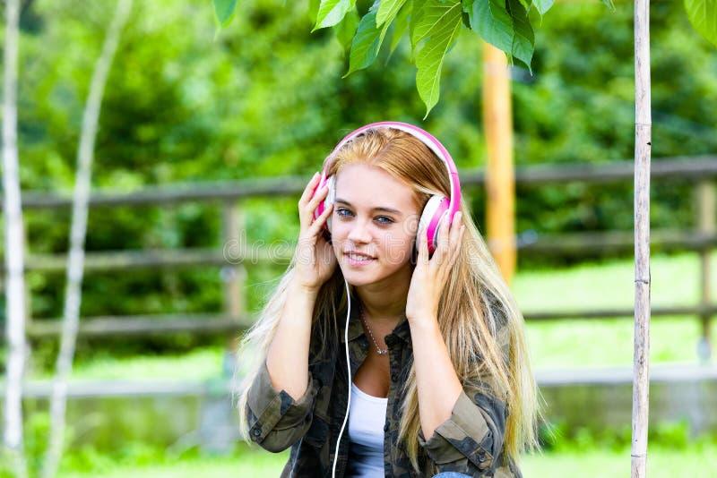 Mujer joven atractiva sonriente que disfruta de música foto de archivo libre de regalías
