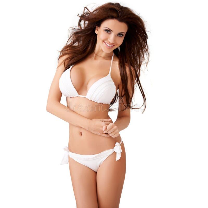 Mujer joven atractiva vivaz en un bikini blanco fotos de archivo