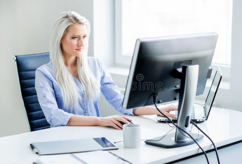 Mujer joven, atractiva y confiada que trabaja en oficina fotografía de archivo libre de regalías