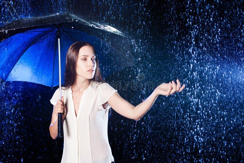 Mujer joven bajo el paraguas Protección contra la lluvia foto de archivo
