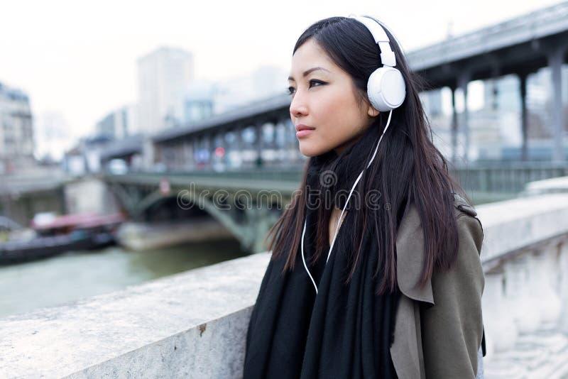 Mujer joven bastante asiática que escucha la música y que mira de lado en la calle fotografía de archivo libre de regalías