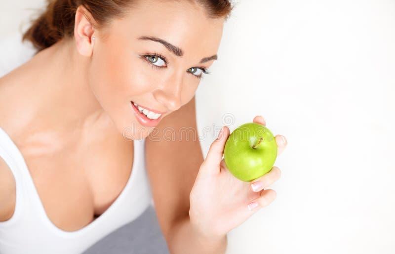 Mujer joven bastante sana que sonríe sosteniendo una manzana verde fotos de archivo