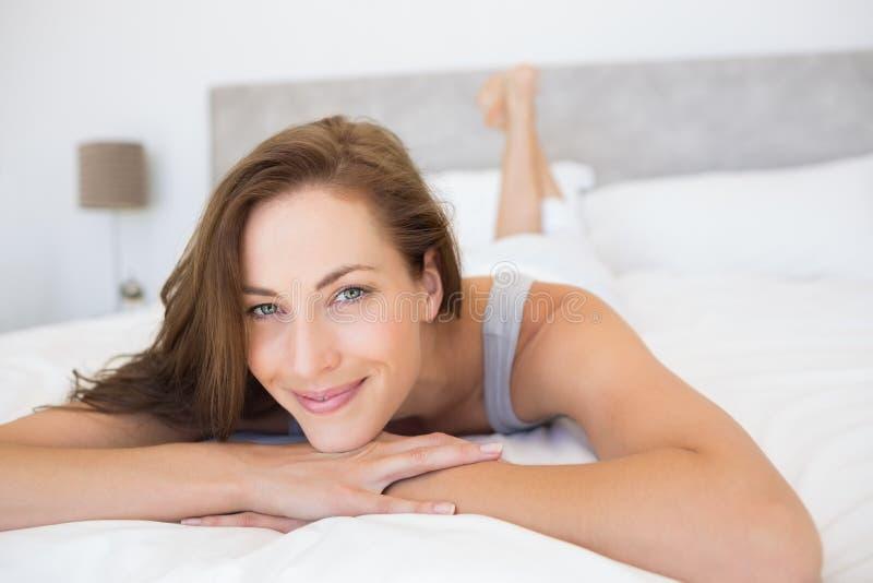 Mujer joven bastante sonriente que miente en cama foto de archivo libre de regalías
