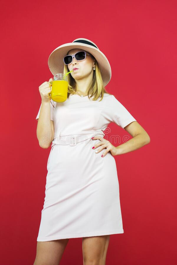 Mujer joven bebiendo un vaso de jugo en el estudio imagen de archivo