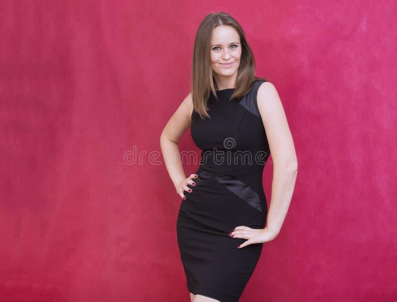 1 mujer joven blanca en vestido negro apretado se coloca en backgroun rojo imagen de archivo