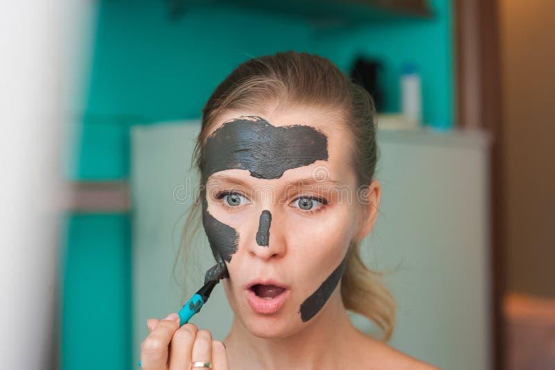 Mujer joven blanca que lleva una mascarilla en casa en un fondo de la turquesa Mujer europea en la máscara negra para el cierre d fotos de archivo libres de regalías
