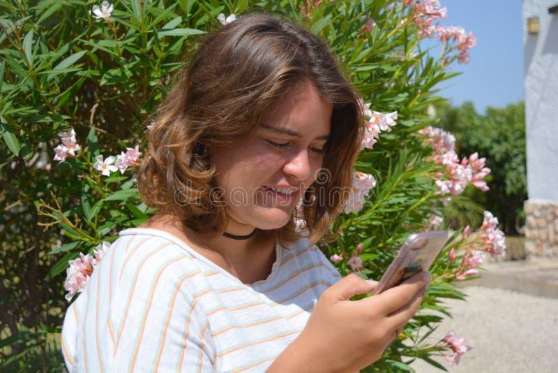 Mujer joven bonita al aire libre, usando un smartphone fotografía de archivo