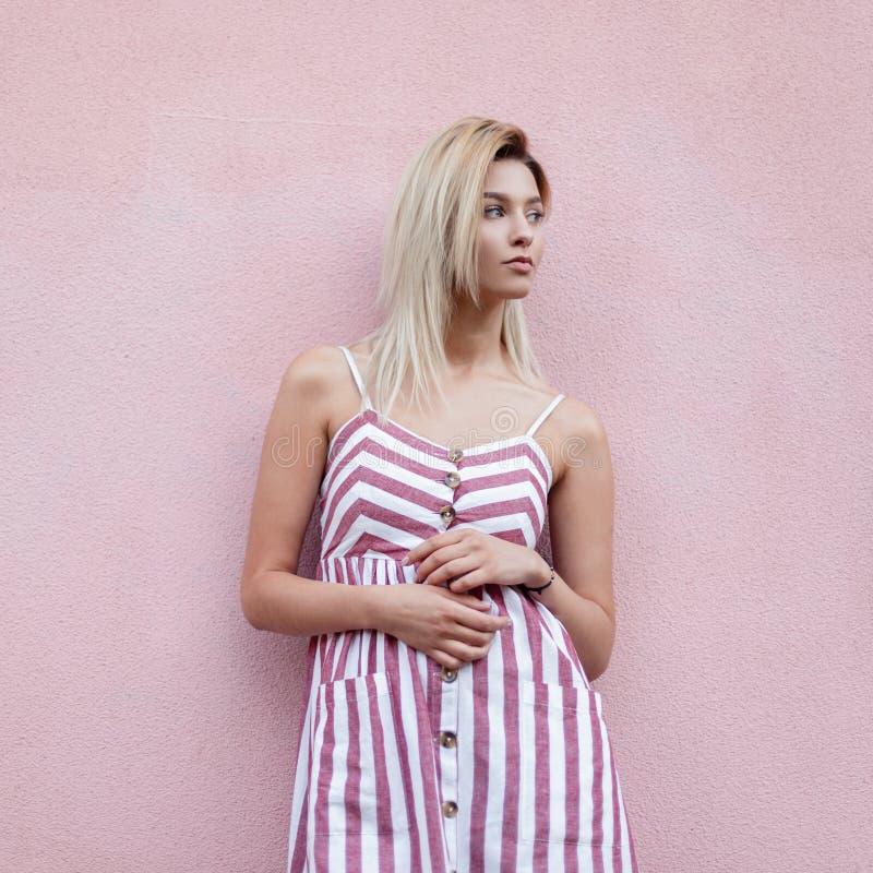 Mujer joven bonita de moda rubia en el vestido rayado rosado de moda que presenta cerca de una pared rosada del vintage en la cal imagen de archivo