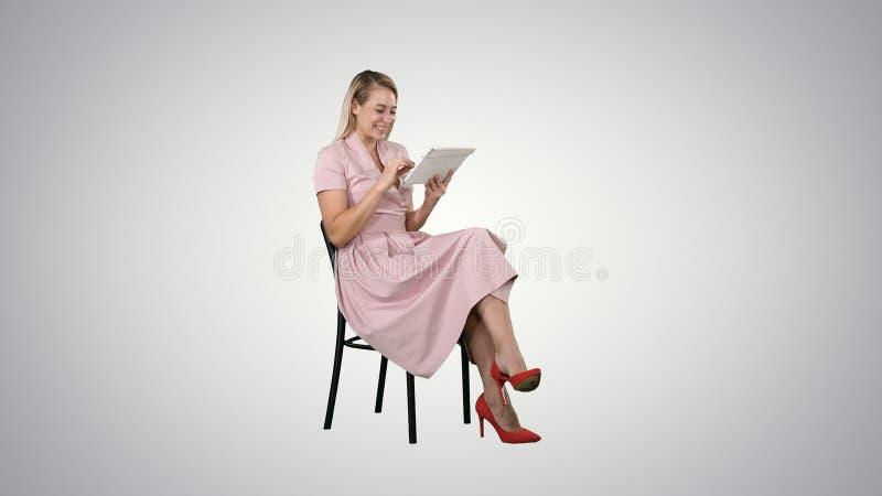 Mujer joven bonita divertida en el vestido rosado que se sienta en una silla y que usa la tableta en fondo de la pendiente fotografía de archivo libre de regalías