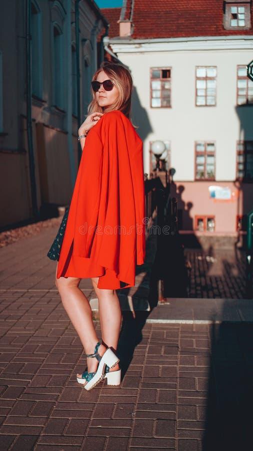 Mujer joven bonita en chaqueta roja en fondo urbano de la calle de la ciudad imagen de archivo