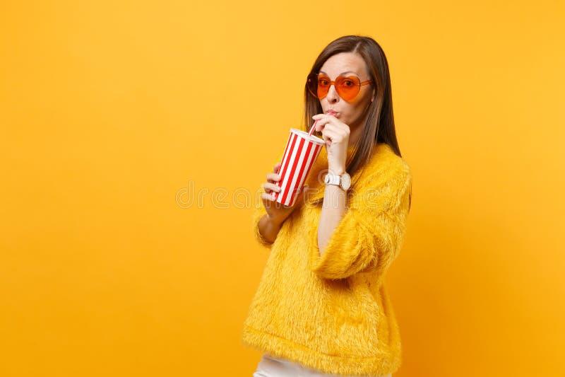 Mujer joven bonita en suéter de la piel y vidrios anaranjados del corazón que bebe la cola o soda de la taza plástica aislada en  fotografía de archivo