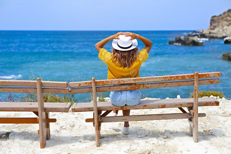 Mujer joven bonita en un sombrero de paja que se sienta en un banco delante del mar fotos de archivo libres de regalías