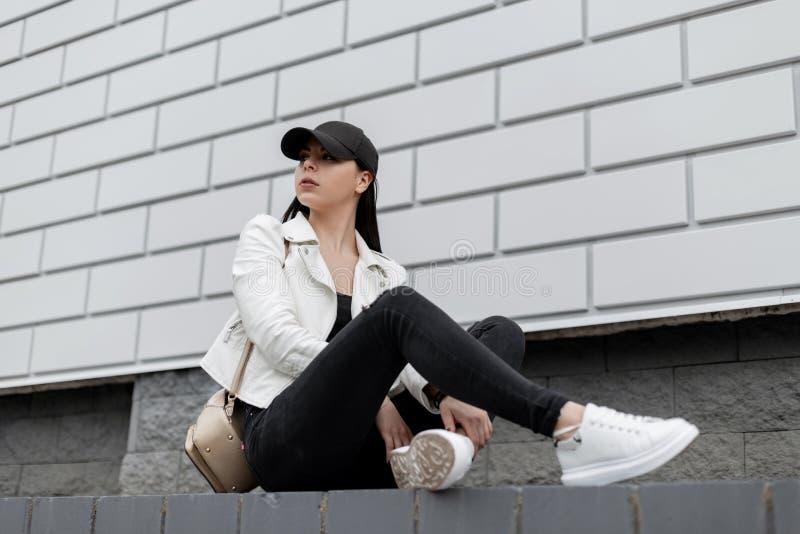 Mujer joven bonita en una chaqueta de cuero elegante en una camiseta en vaqueros negros en las zapatillas de deporte blancas en u foto de archivo