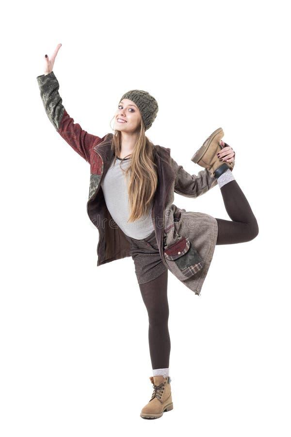 Mujer joven bonita linda en la ropa caliente que se coloca en una pierna que equilibra y que sonríe fotografía de archivo libre de regalías