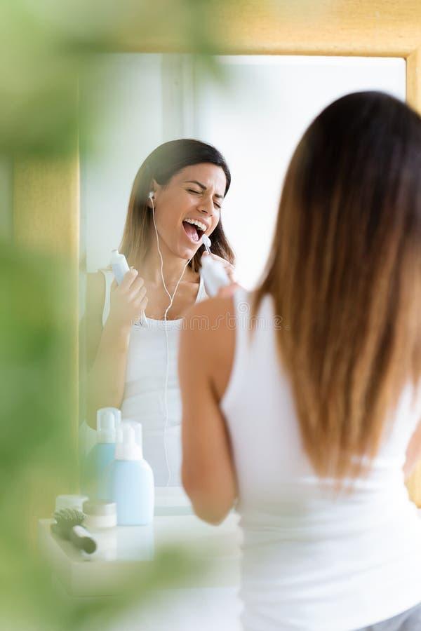 Mujer joven bonita que disfruta de tiempo mientras que cepilla sus dientes en el cuarto de baño en casa imagen de archivo libre de regalías