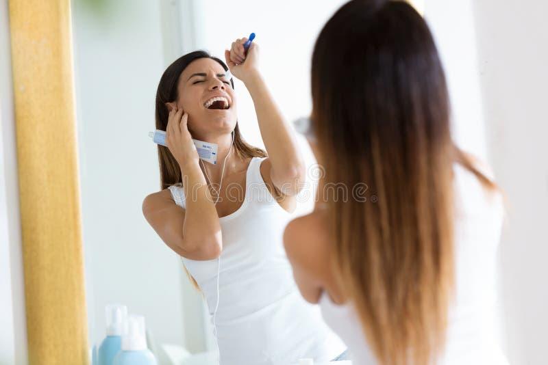 Mujer joven bonita que disfruta de tiempo mientras que cepilla sus dientes en el cuarto de baño en casa imagenes de archivo