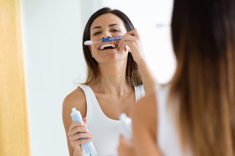 Mujer joven bonita que disfruta de tiempo mientras que cepilla sus dientes en el cuarto de baño en casa imagen de archivo
